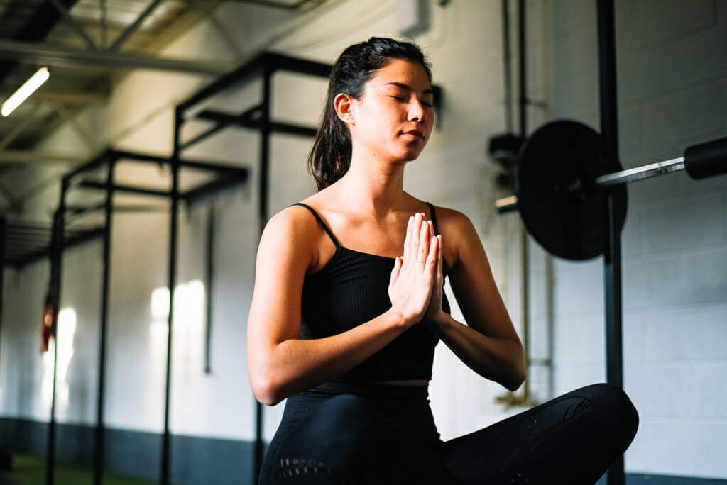 female sat on floor in a gym, practicing yoga.